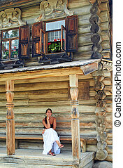 Young woman in front of Old Russian wooden house - Girl...