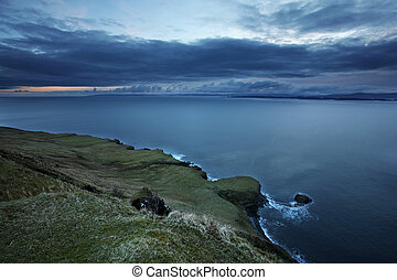 A dramatic sloping shoreline on Isle of Skye in the Outer Hebrides of Scotland, at sunrise