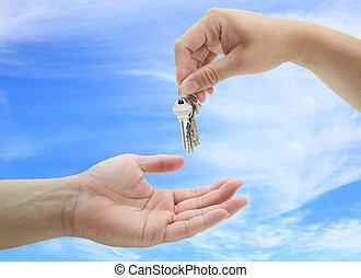 man handing over the set of keys house against blue sky