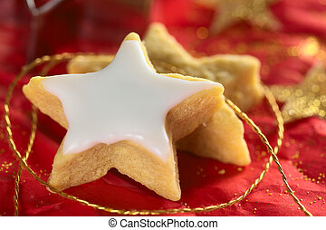 Star shaped cookie with sugar icing on red (Selective Focus,...