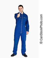 Smiling young mechanic in boiler suit presenting his wrench...