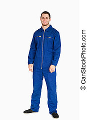 Smiling young mechanic in boiler suit against a white...