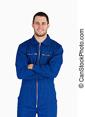 Smiling mechanic in boiler suit with folded arms against a...
