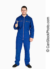 Smiling young mechanic in boiler suit with a wrench against...