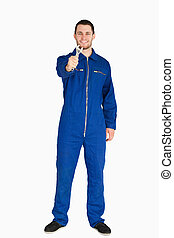 Smiling young mechanic in boiler suit showing his wrench...