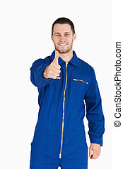Thumb up given by smiling young mechanic in boiler suit...