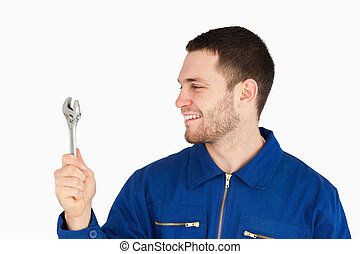 Smiling young mechanic in boiler suit looking at his wrench...