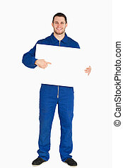 Smiling young mechanic in boiler suit pointing on banner in his hands against a white background