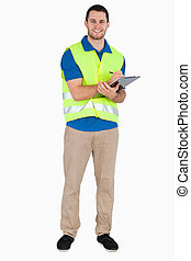Smiling young male with safety jacket taking notes