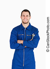 Smiling young mechanic in boiler suit with wrench and arms...
