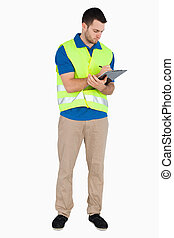 Young male with safety jacket taking notes against a white...