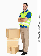 Smiling young delivery man with arms folded