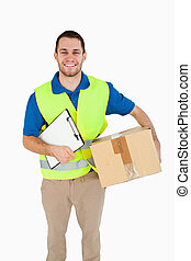 Smiling young delivery man with parcel and delivery note...