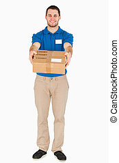 Smiling young salesman handing over parcel