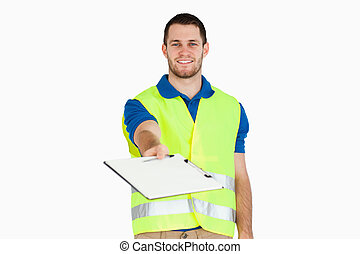 Smiling young delivery man asking for signature on delivery bill against a white background