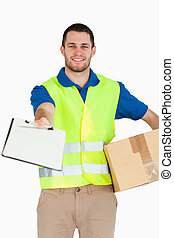 Smiling young delivery man with packet asking for signature...