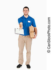 Smiling young salesman with parcel asking for signature