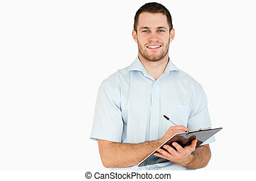 Smiling young post employee taking notes on clipboard...