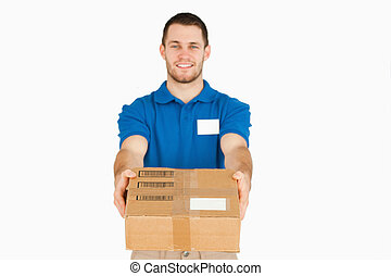Smiling young sales assistant handing over parcel against a...