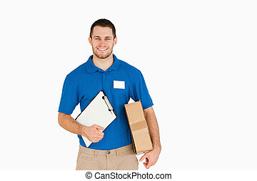Smiling young salesman with parcel and clipboard against a...