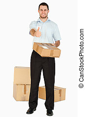 Smiling young post employee with parcels giving thumb up