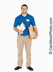 Smiling young salesman with clipboard and parcel against a...