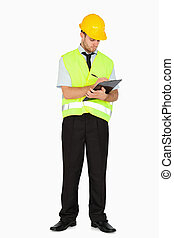 Young foreman in safety jacket taking notes on clipboard