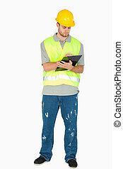 Young construction worker taking notes on his clipboard