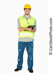 Smiling young construction worker taking notes against a...