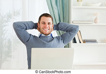 Smiling businessman leaning back in his homeoffice - Smiling...