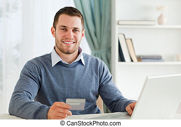 Smiling male with credit card at his laptop - Smiling young...