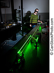female scientist doing research in a quantum optics lab -...