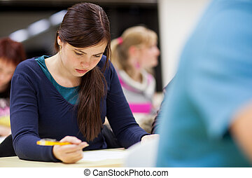 pretty, female college student sitting in a classroom full of students during class (shallow DOF; color toned image)