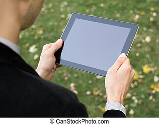 Businessman Holding A Tablet PC - Businessman in a park...