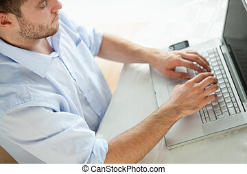 Businessman typing on laptop - Young businessman typing on...
