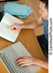 Student researching on the internet - Male student using...