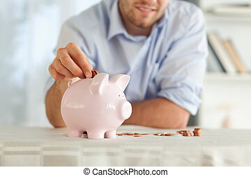 Change being put into piggy bank - Small change being put...