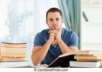 estudante, sentando, seu, escrivaninha, pensando