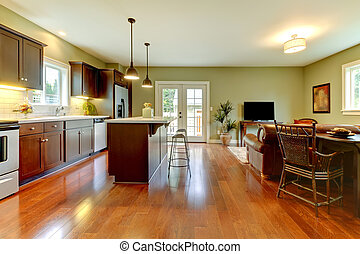Modern new brown kitchen with cherry floor and living room..