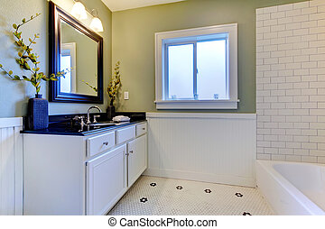 Classic green and white bathroom with ceramic tiles.