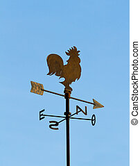Wind cock direction on blue sky