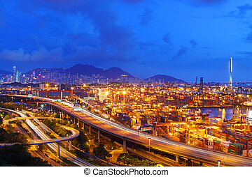 Busy traffic in Hong Kong at night with container terminal...
