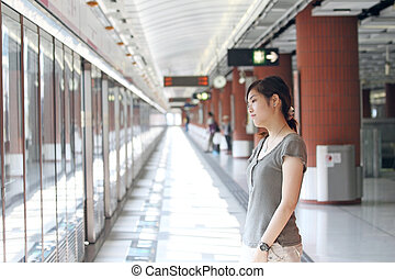 Asian woman waiting for train
