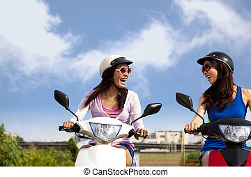 Happy girls having road trip on a scooter