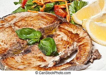 cooked swordfish served with salad and lemon