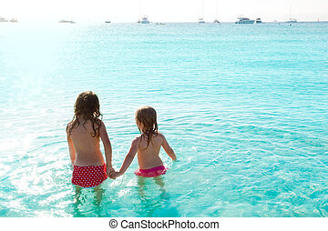 children girls rear view in the beach at sunset
