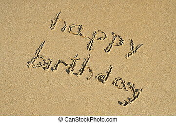 happy birthday written on the sand of a beach