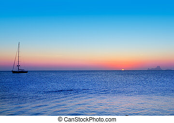 Ibiza sunset from Formentera with Es Vedra and sailboat in...