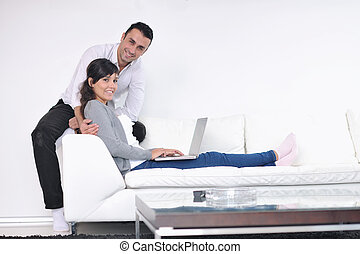 joyful couple relax and work on laptop computer at modern...