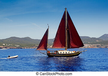 Ibiza Red sails sailboat in Sa Talaia coast of Balearic...